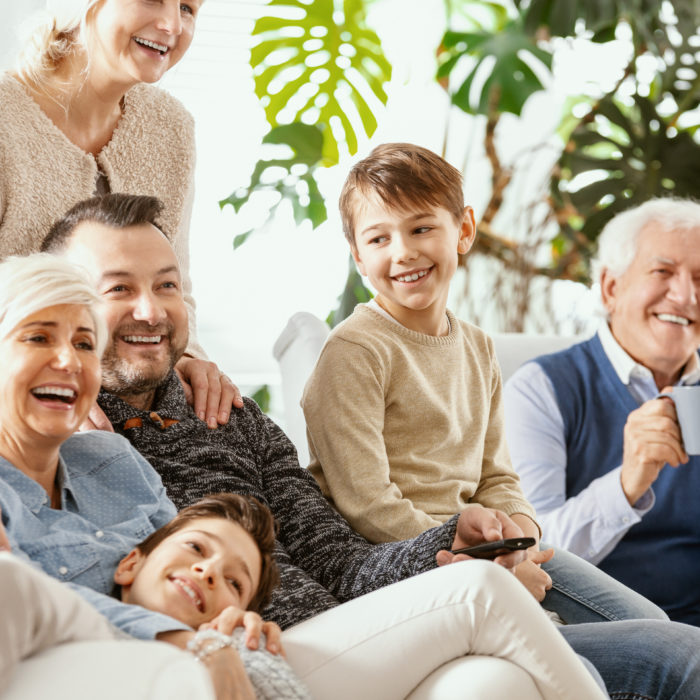 Smiling parents and kids watching television with happy grandfather